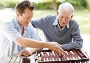 young and older man playing backgammon
