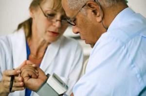 woman doctor taking mans blood pressue